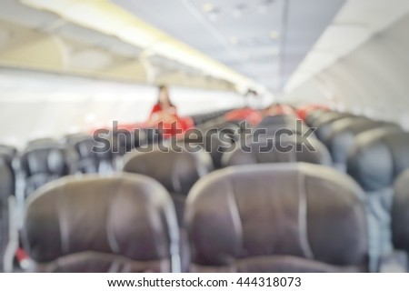 Blur abstract background empty seat rows in an airplane cabin. Blurry view of air hostess waiting to welcome passengers on board. Defocus cabin crew on aircraft.
