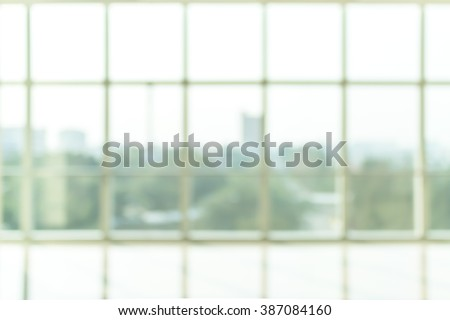 Blur abstract background interior view looking out through empty office lobby corridor walk way glass curtain wall with frame and light: Blurry reception hall to building window door exterior facade - stock photo