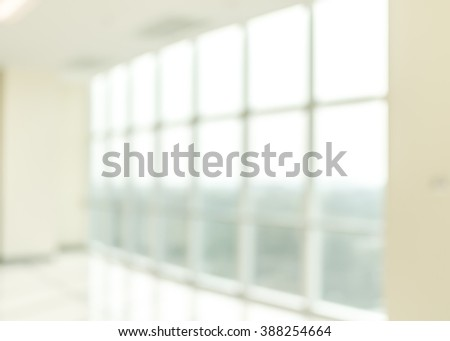 Blur abstract background interior view looking out through empty office lobby corridor walk way glass curtain wall frame with sun light: Blurry reception hall to building window door exterior facade - stock photo
