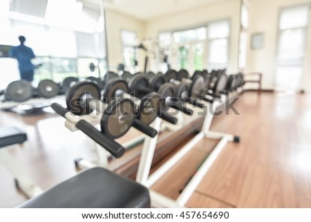 Blur abstract background modern fitness center lifestyle with health exercise equipment & dumbell: Blurry perspective view gym room: Gymnasium indoor space for diet, bodybuilding training - stock photo