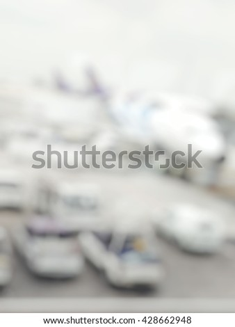 Blur abstract background of airplane parking at gate wait to load passengers inside. Blurry view of service trucks around commercial plane to maintenance system. - stock photo