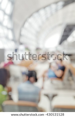 Blur abstract background of departure airport lounge area with travellers. Blurry view of passengers waiting in depart gate. Defocus image international airport interior. - stock photo