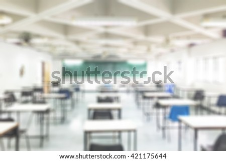Blur abstract background of empty examination room for undergraduate students. Blurred view of  exam hall with no student. Blurry view of study chairs in classroom of university or campus with nobody. - stock photo