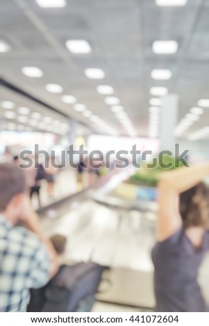 Blur abstract background of family travellers waiting for luggage in baggage claim at international airport. Blurry view people wait at conveyer belt for suitcase bokeh effect. - stock photo