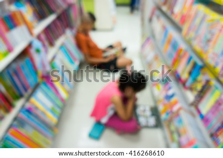 Blur abstract background of kid scan reading cartoon in bookstore on the floor of shop, Blurry view of children read books near bookshelf - stock photo