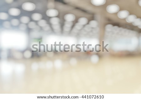 Blur abstract background of travellers waiting for luggage in baggage claim at international airport. Blurry view people wait at conveyer belt for suitcase bokeh effect. - stock photo