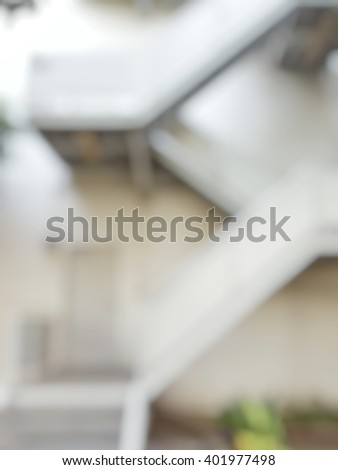 Blur abstract background of white emergency exit door. Blurry view of door with stairs for fire escape urgent out of building. - stock photo