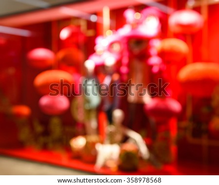 Blur abstract motion of a fashion boutique/outlet windows display with mannequin and Chinese New Year red lantern decoration in an Asian shopping mall - stock photo