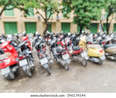 Blur abstract of a university parking lot with varieties of motorcycles in many brands and colors. Vietnam is the world second highest motorcycle-owning country with more than 42mil registered ones. - stock photo
