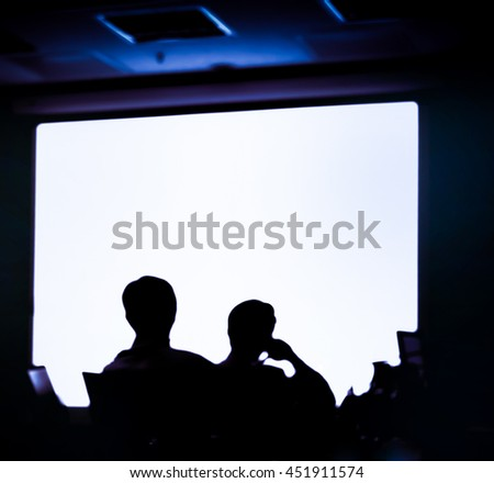 Blur audience sitting in meeting room  with  screen, silhouette style