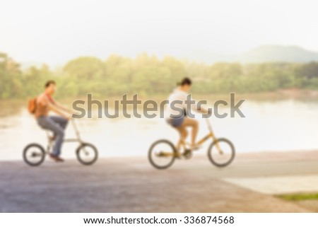 Blur background man and women   ride bicycle near river.