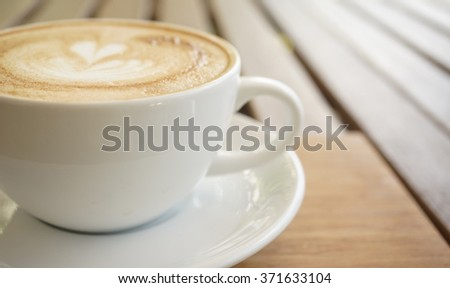 blur background of a cup of coffee on the wooden table in the coffee shop