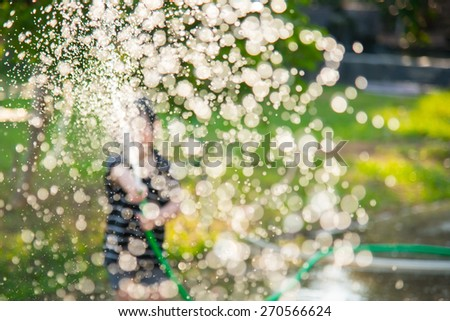 Blur background of Asian child playing with water hose outdoors in the garden at the backyard of the house on a hot sunny summer day - stock photo