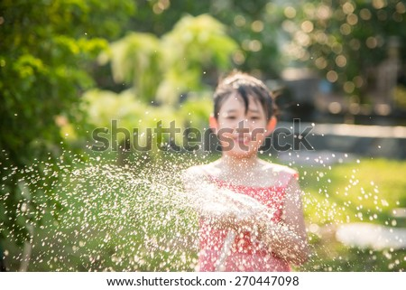 Blur background of Asian girl playing with water hose outdoors in the garden at the backyard of the house on a hot sunny summer day - stock photo