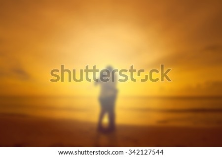 blur background of couple kissing on the beach at sunset - stock photo