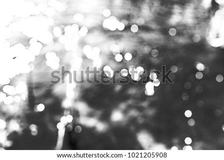 Blur bokeh background of water with flecks of sunlight. Monochrome photo