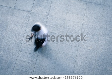 blur business man walking and using smart phone on the street - stock photo