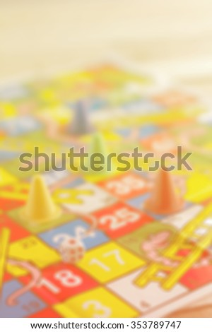 blur Colored board game figures with dice on wooden board