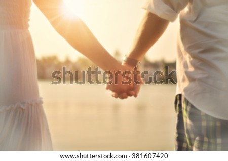 Blur couple holding hand on tropical sunset beach with sun light abstract background.