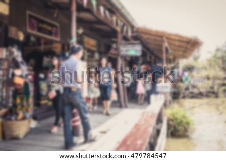 Blur effect of floating market has a many foreign visitors with varieties of Thai clothes and Thai food