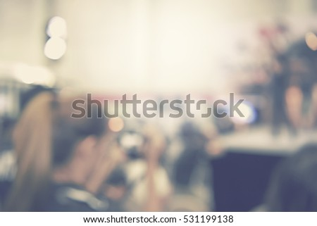 blur event seminar with activity on stage - blurred female taking photo background -  bokeh light vintage tone - business concept