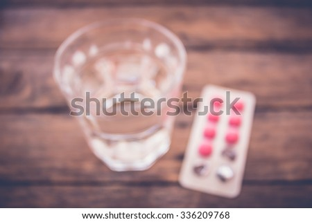 Blur glass of water with medicines on wood background - stock photo