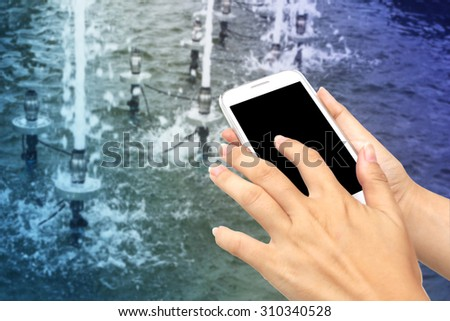 blur hand touching mobile phone with blur water drop from fountain in pool background - stock photo