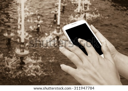 blur hand touching mobile phone with blur water drop from fountain in pool background  ,vintage tone - stock photo