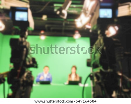 blur image A television presenter in a TV camera in studio a green