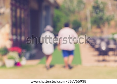 Blur image of a  couple lovers holding hands walking away in the garden at Thailand, summer holiday background concept - retro style - stock photo