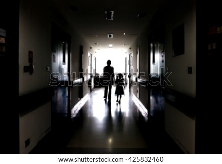 Blur image of a mother and daughter walking on the dark corridor in the hospital. - stock photo