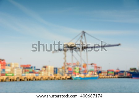 Blur image of cargo ship and large crane operating at the seaport - stock photo
