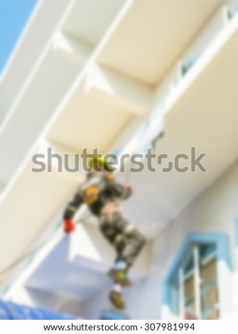 blur image of  Firefighter practice rappelling on tall building. - stock photo