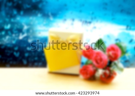 blur image of gift box with tag and red rose with blur drop on mirror background - stock photo