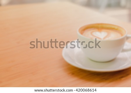 Blur image of hot coffee on wood table for background  - stock photo