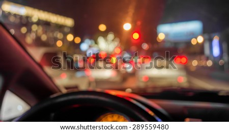 blur image of inside cars with bokeh lights from traffic jam on night time. - stock photo