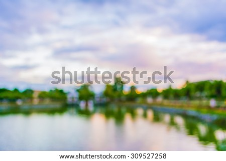 blur image of lake and sunset sky in background . - stock photo