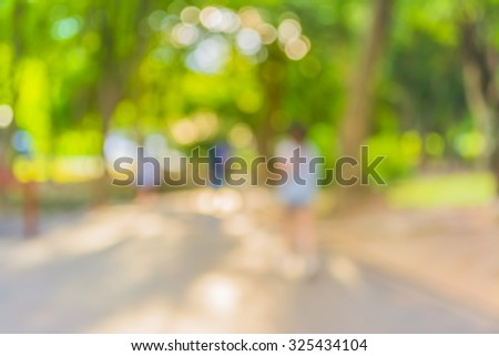 Blur image of people activities in park with bokeh on day time for background usage. - stock photo