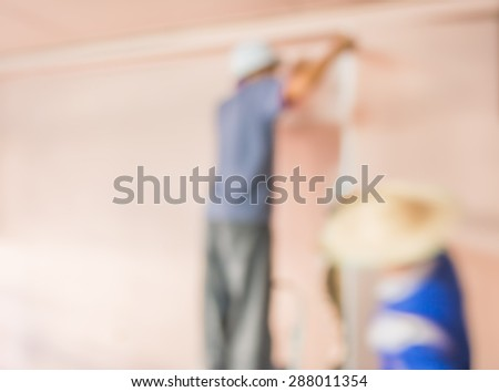 blur image of people  fixing house wall for background usage. - stock photo