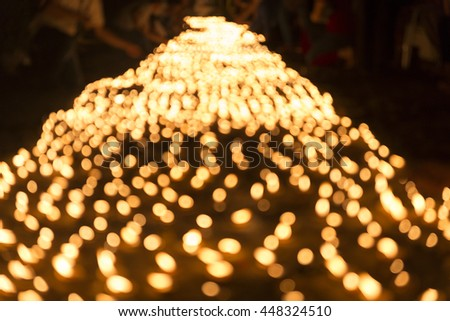 blur image of people light candle to pay respect to buddha relic at buddhist temple - stock photo