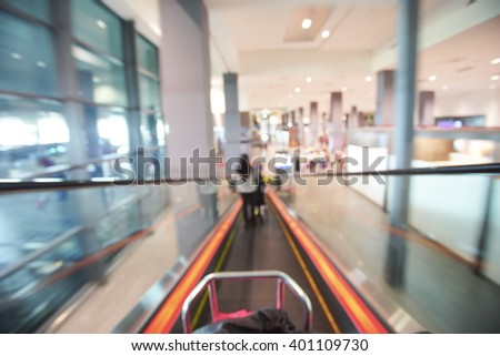 Blur image of people walking down the escalator at airport - stock photo