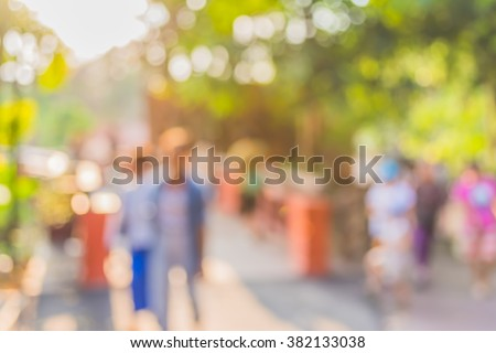 blur image of people walking in the park  with bokeh for background usage . - stock photo
