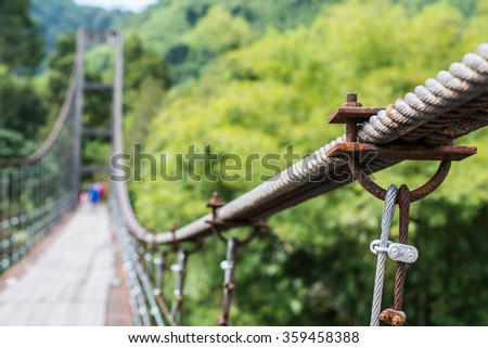 Blur image of suspension bridge in forest for background