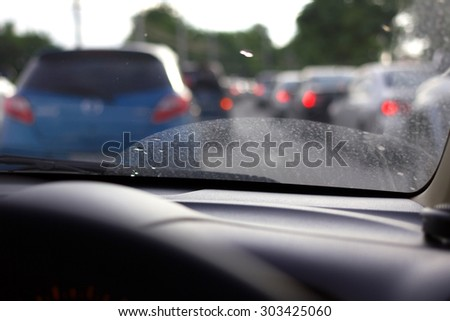Blur image of the dirty windshield on traffic jam day.