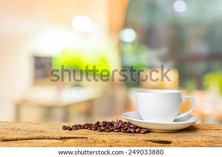blur image of  white coffee cup with indoor living room in background  - stock photo