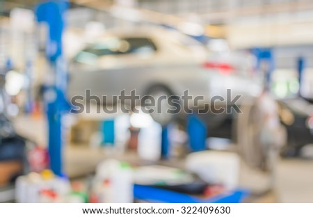 blur image of worker fixing car in the garage for background usage. - stock photo