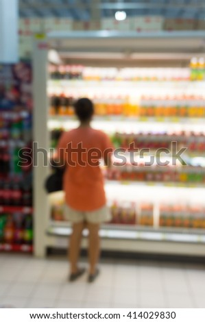 blur image of young woman shopping for juice in produce departme