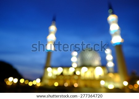 Blur image or bokeh light of Shah Alam Mosque night scenery during blue hour.  Intentionally added blue tones to make the it look more atmospheric. - stock photo