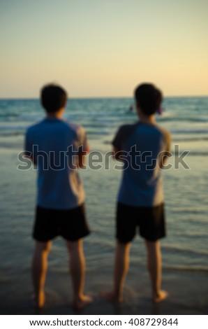 blur image, two man enjoy at sunset beach - stock photo