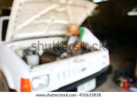 Blur male trying to repair a car engine, looking inside open bonnet - stock photo